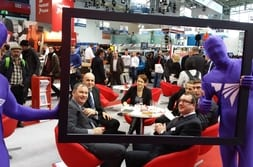 BAU MUNICH 2015 – Group photo of customers in PVC-U window frame with profine mascot